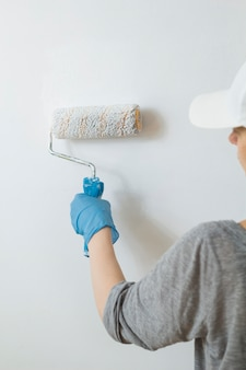 The woman painter paints the wall with a roller in white.