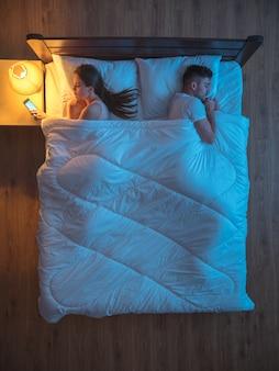Женщина по телефону на кровати рядом с мужем. ночное время. вид сверху