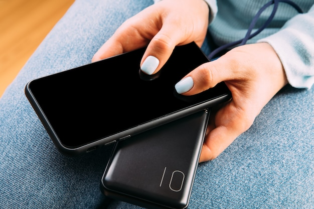 女性はオフィスや自宅の電話で充電器を接続しました。パワー・バンク。