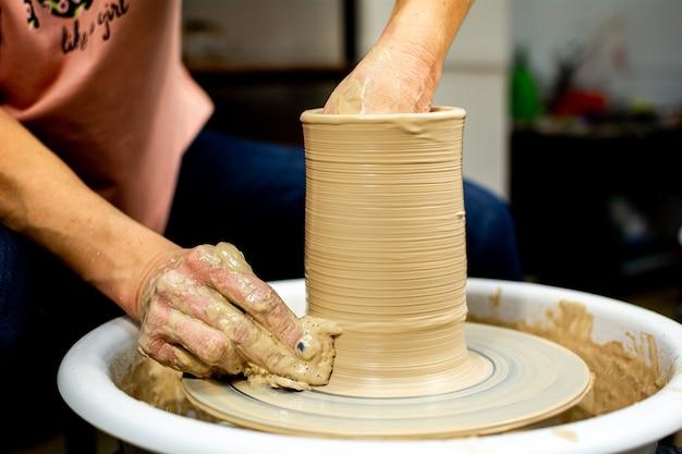 Руки женщины-гончара образованы глиняным горшком на гончарном круге. гончар работает в мастерской.