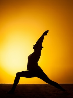 夕日の光の中でヨガを練習する女性