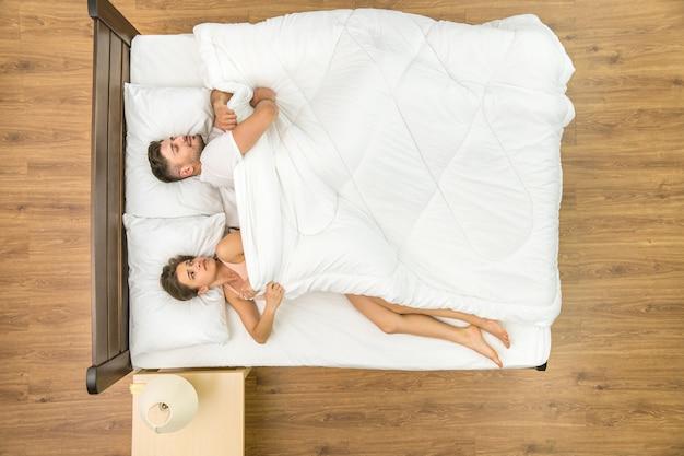 女性はベッドの上で毛布を引っ張る。上から見る