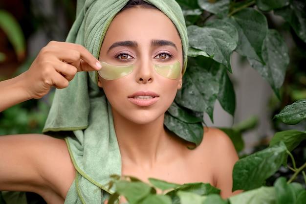 美しさの目の目のスキンケアのための緑のパッチの目の下に置かれた女性、