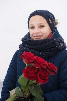 여자는 발렌타인 데이에 빨간 장미 꽃다발을 선물로 받았다.