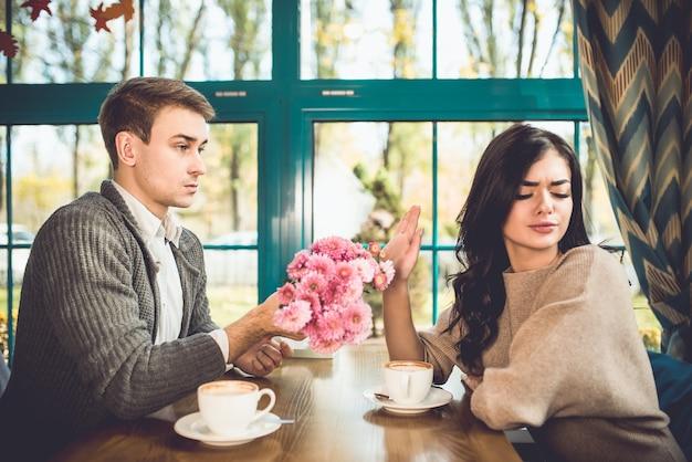 Женщина отвергает цветы от своего парня в ресторане