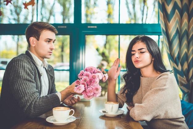 Женщина отвергает цветы от своего мужчины в ресторане