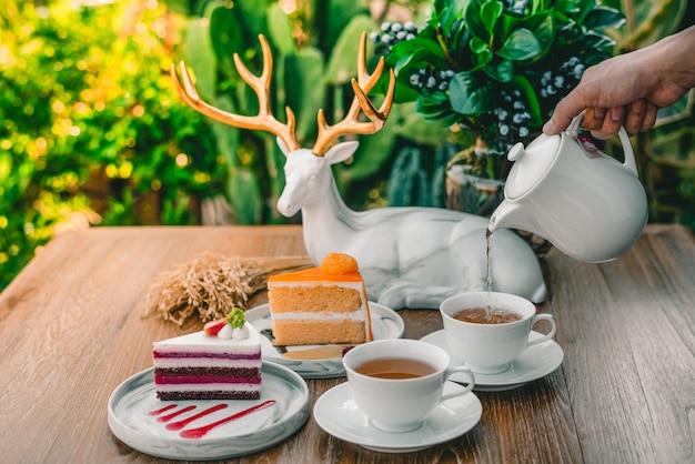 女性の手は、朝の熱いお茶とケーキを注いでいます。