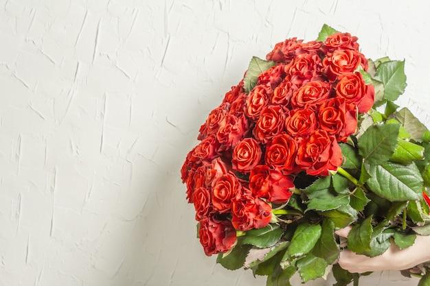 女性の手は、新鮮な赤いバラの緑豊かな花束を持っています