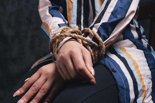 여자의 손은 밧줄로 묶여있다