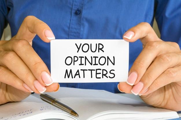 女性の手はあなたの意見の問題、ビジネスと金融の概念のテキストが付いた名刺を持っています