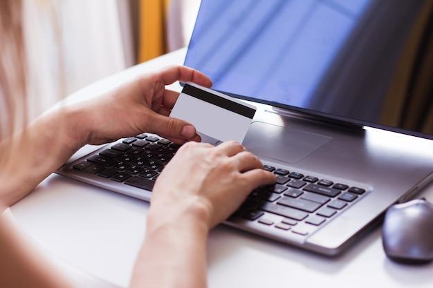 女性の手はクレジットカードを持って、ラップトップを使用しますオンラインストアオンラインショッピングセール