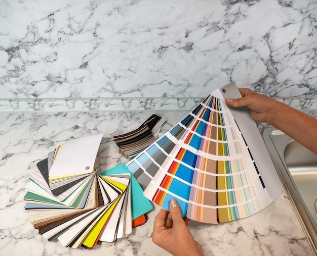 В руках женщины палитра цветов и образец материалов для изготовления кухонной мебели.