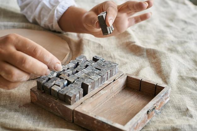 女性の手が粘土に印刷される文字を拾う