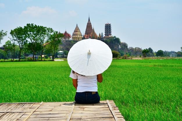 Женщина сидела лицом к спине белого зонта на деревянном мостике.