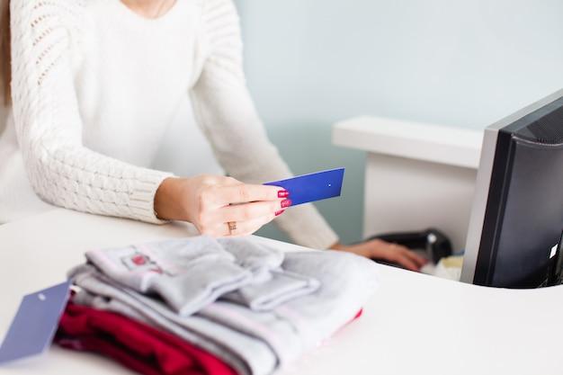 여성 판매자가 바코드 가격을 확인합니다.
