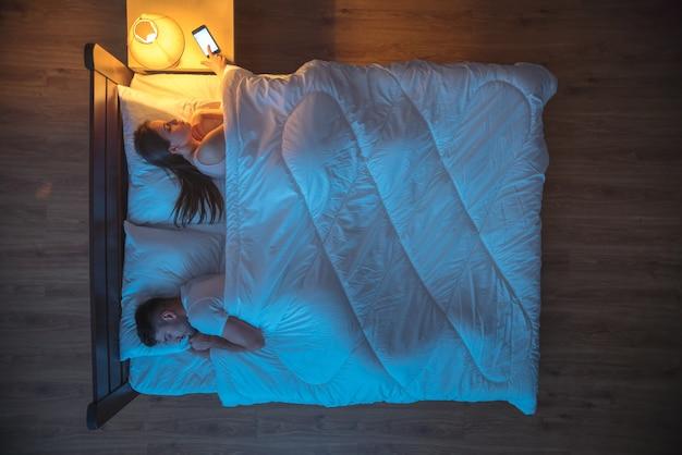 Женщина поставила будильник на кровати рядом с мужем. ночное время. вид сверху