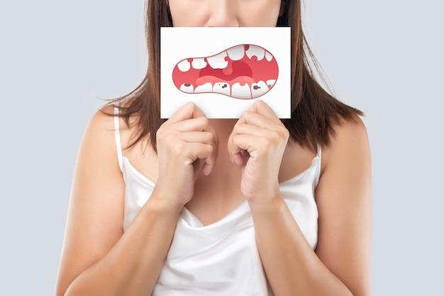 女性は白い紙に虫歯の問題の写真、健康歯茎と歯のイラストを示しています。腐った歯。