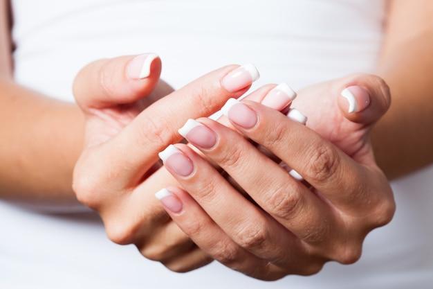 그 여자는 서로 손을 대고 있는 아름다운 프랑스 매니큐어를 보여줍니다