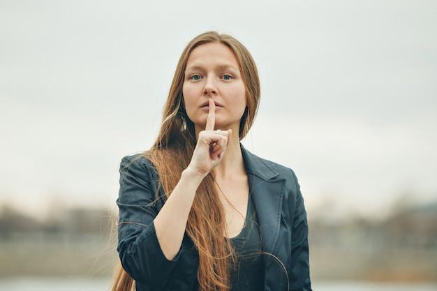 여자는 조용히 말하는 신호를 보여줍니다. 감정, 문제의 표현 개념.