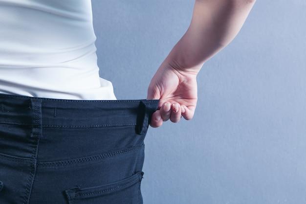 女性は彼女がどれだけ体重を減らしたかを示しています