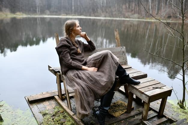 女性は湖のほとりに座っています。孤独な女性。湖のある秋の森。