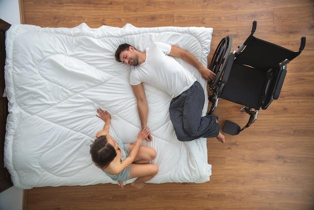 ベッドの上の障害者の男性の近くに座っている女性。上からの眺め