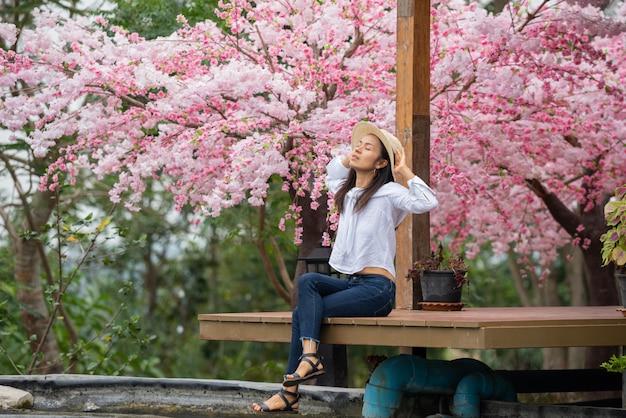 Женщина сидит под вишневым деревом