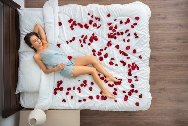 バラの花びらとベッドで寝ている女性。上からの眺め