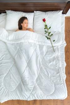 ベッドの上でバラと寝ている女性。上からの眺め
