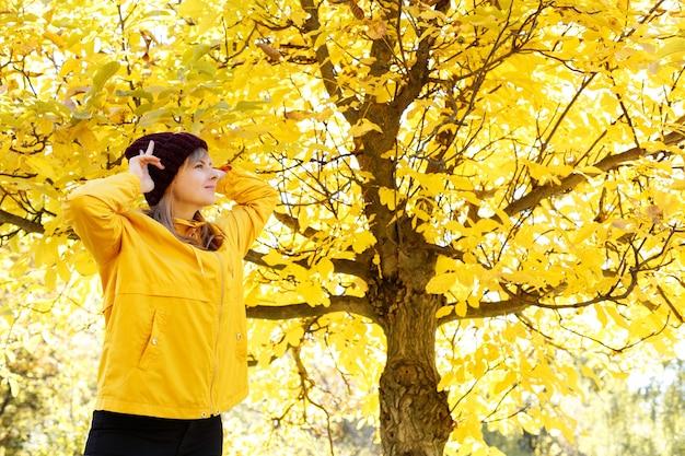 黄色い紅葉の前で女性が微笑んで右を向いている。テキスト用の空き容量