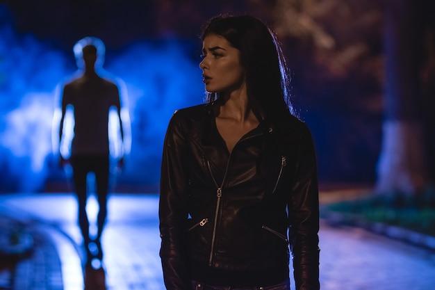 Женщина стоит в темном переулке на фоне дымящегося мужчины. ночное время