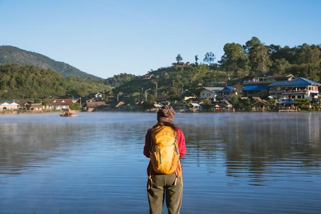 湖の近くに立っている女性は、霧の自然の美しさを楽しんで笑っていました。