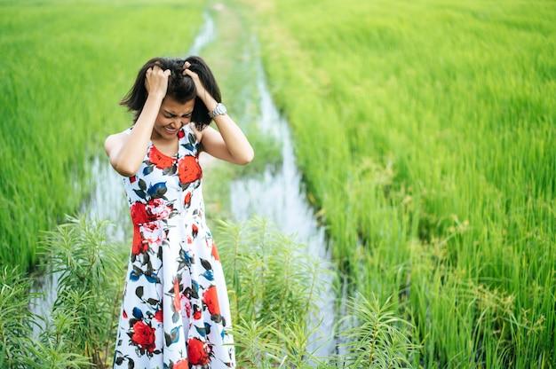 女性は緊張して立ち、手は牧草地で髪を抱えた