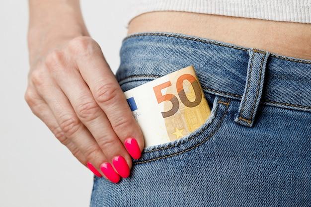 女性はブルージーンズのポケットから50ユーロの紙幣を受け取ります。金融および商業の概念。