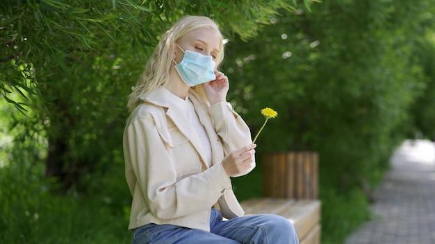 女性は医療用マスクを脱いで黄色いタンポポを嗅ぎます。流行中の屋外レクリエーション。 4k uhd