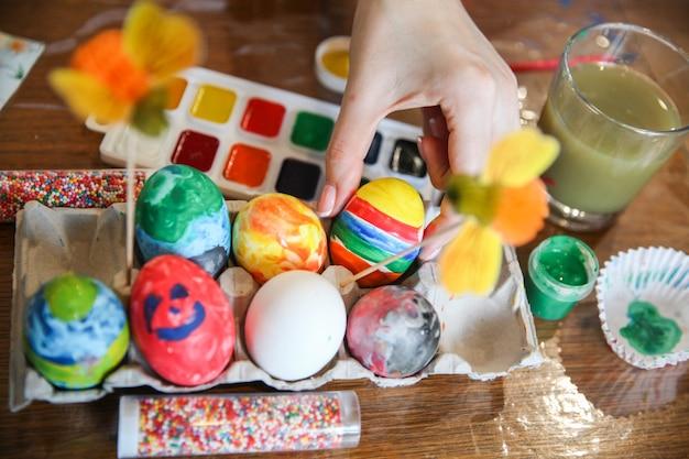 여자는 부활절 장식을 위해 테이블에있는 공예 스탠드에서 계란 하나를 가져옵니다.