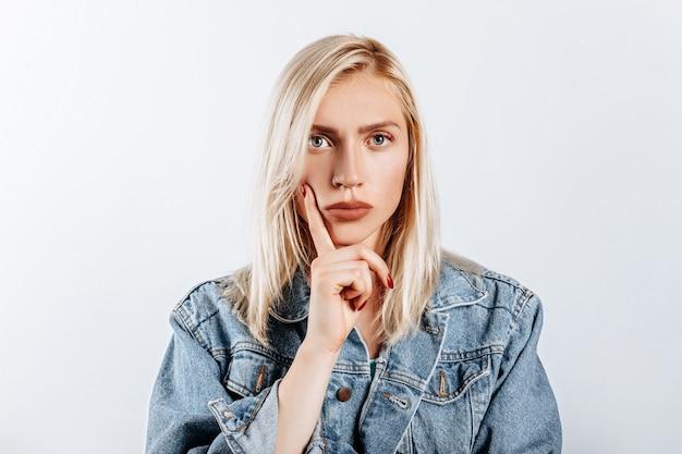Женщина задумалась над выбором и нахмурила брови на сером изолированном фоне. Premium Фотографии