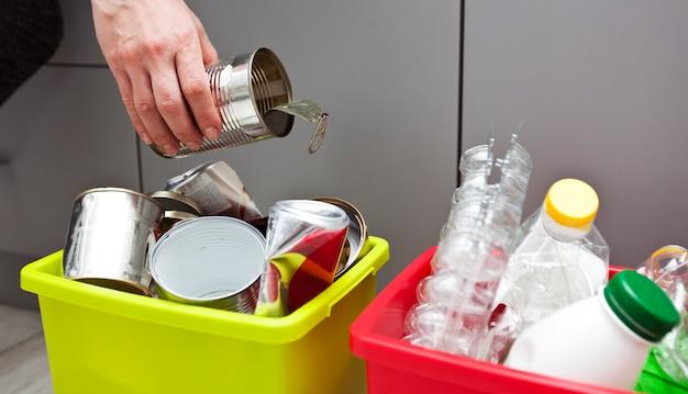 Женщина бросает металлический контейнер в один из четырех контейнеров для сортировки мусора