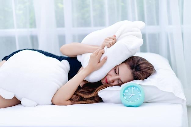 아침에 알람 시계가 울리는 동안 여자는 귀에서 베개를 took습니다. 제 시간에 일하러 가기 위해 깨어 난다는 생각