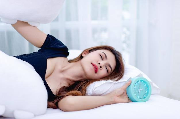 朝目覚まし時計が鳴っている間、女性は枕を耳から外しました。起きて時間通りに仕事に行くというアイデア