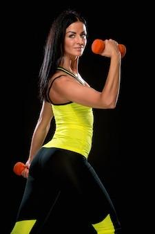 Женщина тренируется против черной стены с красными гантелями