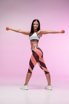 ピンクのスタジオに対して訓練する女性