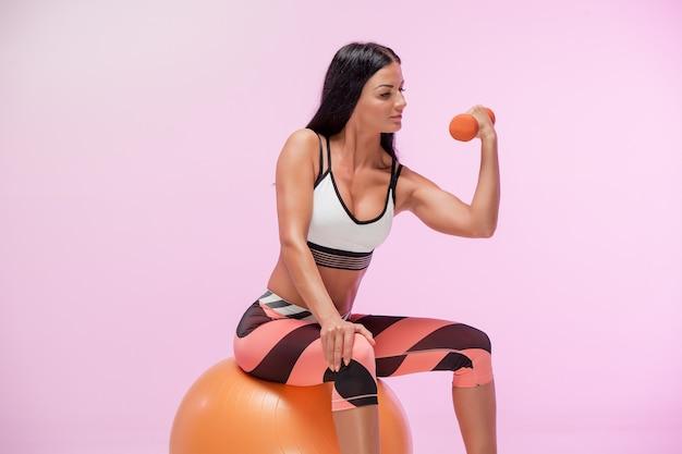 Женщина, тренирующаяся против розовой студии