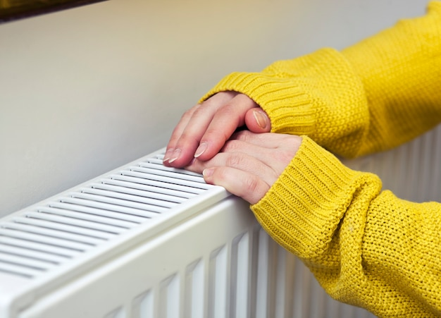 Женщина греет руки на радиаторе