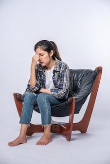女性は病気で、椅子に座って、手で頭に触れました。
