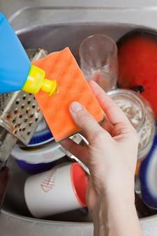 女性は台所で陶器を洗う
