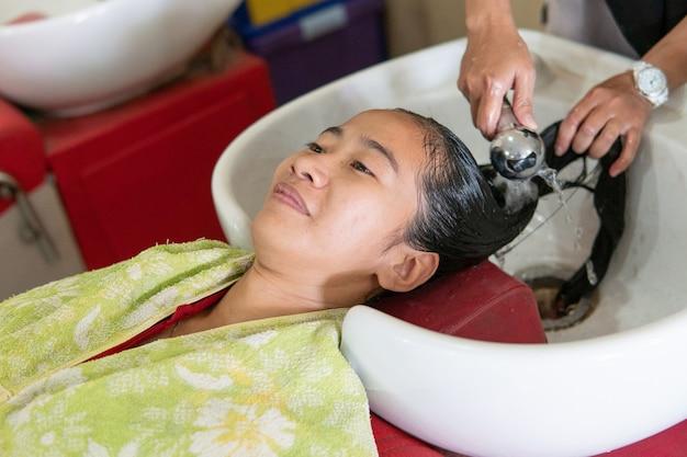 Женщина моет волосы парикмахером в салоне красоты