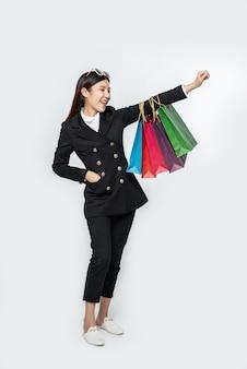 買い物に行くために、たくさんのバッグと一緒に暗い服を着ている女性