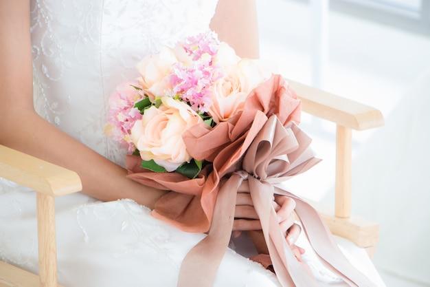 Женщина в платье невесты сидит на стуле и держит букет цветов, готовясь к предсвадебной фотосессии.