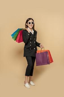 여자는 쇼핑하러 가기 위해 많은 가방과 함께 어두운 옷과 안경을 착용합니다.
